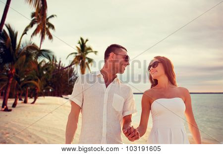 love, people, travel, summer and relations concept - smiling couple wearing sunglasses walking outdoors over tropical beach background
