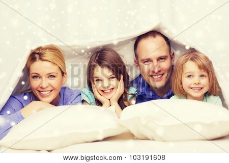 family, children, comfort, bedding and home concept - happy family with two kids under blanket over snowflakes background