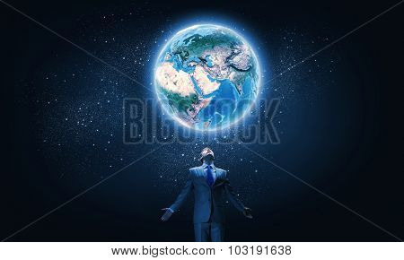 Young businessman and Earth planet above. Elements of this image are furnished by NASA