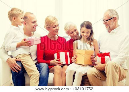 family, holidays, generation, christmas and people concept - smiling family with gift boxes sitting on couch at home
