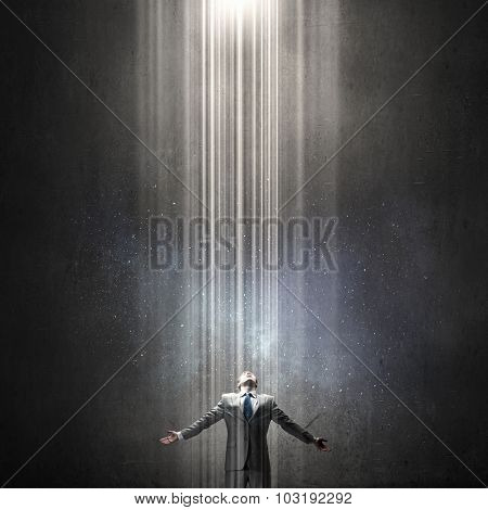 Businessman with hands spread apart standing in light coming from above