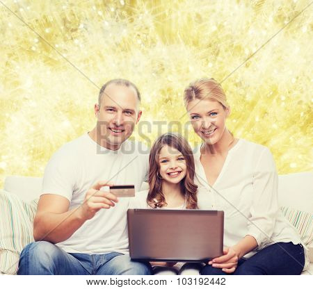 family, holidays, shopping, technology and people concept - happy family with laptop computer and credit card over yellow lights background