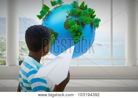 Cute little boy with paper airplane against earth floating in room