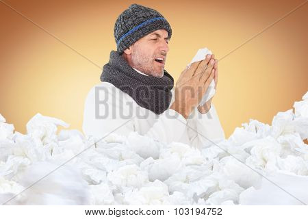 Sick man in winter fashion sneezing against orange vignette