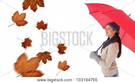 Smiling brunette holding red umbrella against autumn leaves pattern