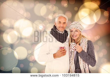 Portrait of happy couple drinking hot coffee against light glowing dots design pattern