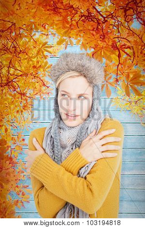 Attractive blonde wearing a warm hat against autumn leaves pattern