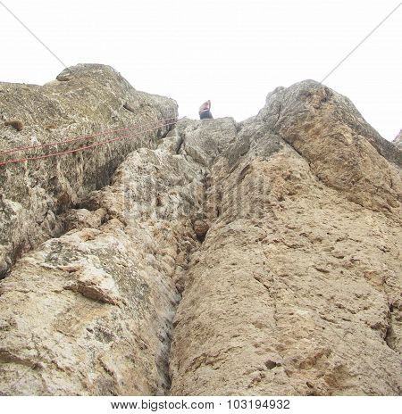 Young man climbing on the mountain face