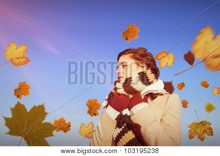 Thoughtful woman in winter clothes against bright blue sky