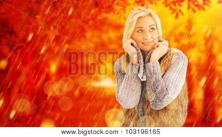 Blonde in winter clothes smiling against autumn scene