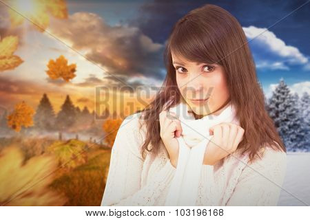 Brunette in winter clothes smiling at camera against autumn changing to winter