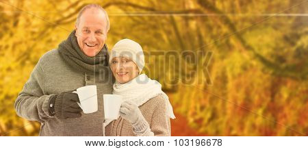 Happy mature couple in winter clothes holding mugs against peaceful autumn scene in forest
