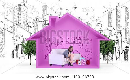 Cute woman sitting on couch taking off her shoes against house shape with kitchen sketch