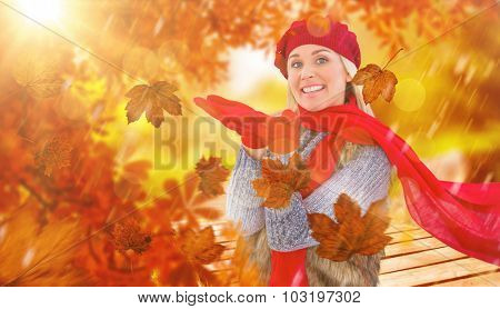 Blonde in winter clothes with hands out against wooden trail across countryside