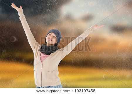 Smiling brunette standing arms open against country scene