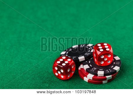 Red dice and chips on green table