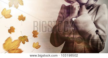 Attractive woman wearing a warm coat with hood raised against autumn leaves pattern