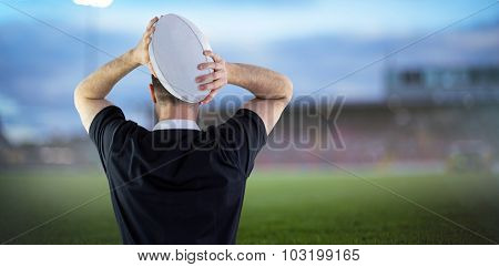 Rugby player running with the rugby ball against pitch
