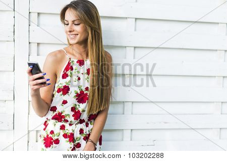 Beautiful Young Woman Using Phone While Leaning Against A White Wall