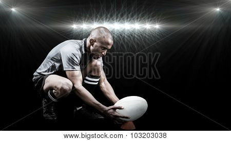 Rugby player keeping ball on kicking tee against spotlight