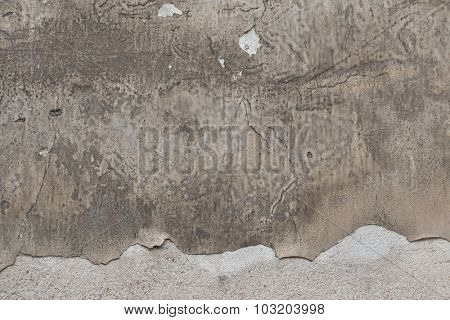 Old grey stucco wall with cracked plaster. Background texture.