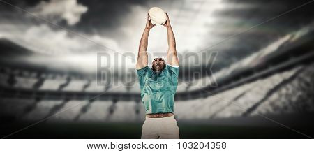 Rugby player catching the ball against rugby arena