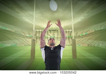 Rugby player catching the ball against linear background