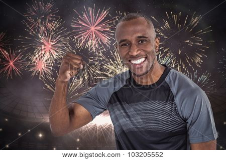 Portrait of sportsman cheering after success in rugby against fireworks exploding over football stadium