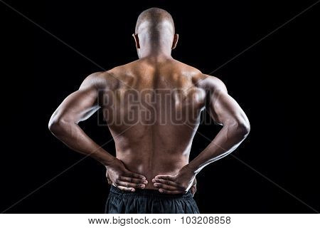 Rear view of athlete stretching with hand on hip against black background