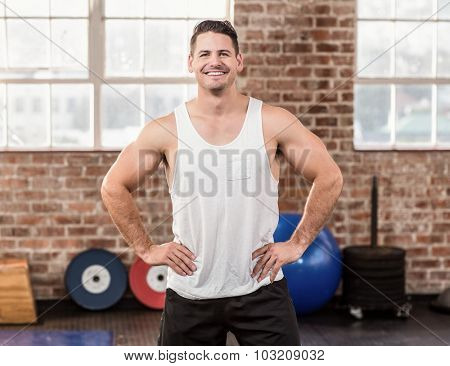 Smiling muscular man with hands on hips in crossfit gym
