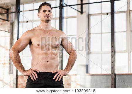 Shirtless muscular serious man posing in crossfit gym