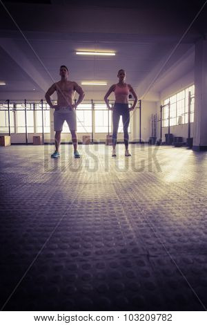 Crossfit couple facing camera with hands on hips in crossfit gym