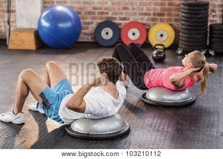 Fit couple doing abdominal crunches in crossfit gym