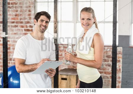 Muscular woman watching her results on clipboard in crossfit gym