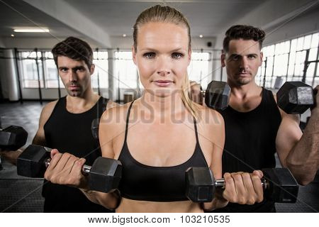 Fit people facing to the camera in crossfit gym