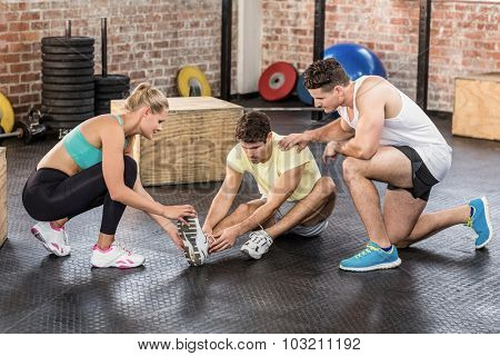 Muscular man having an ankle injury in crossfit gym