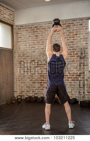 Rear view of man holding kettlebell at the gym