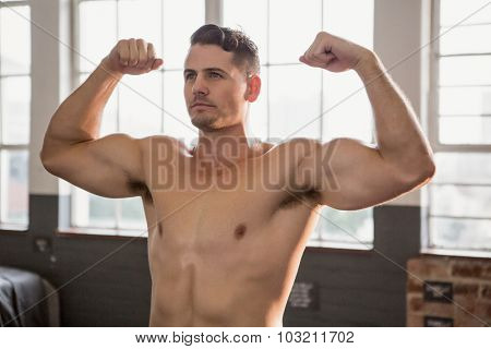 Muscular man flexing muscles at the gym