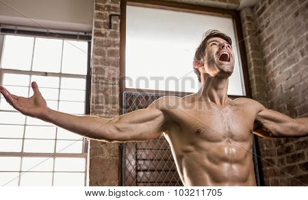 Muscular man with arms stretched at the gym