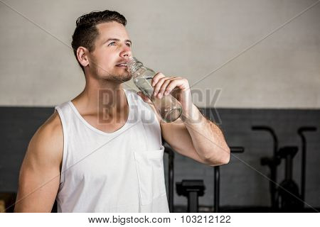 Muscular man holding bottle at the gym