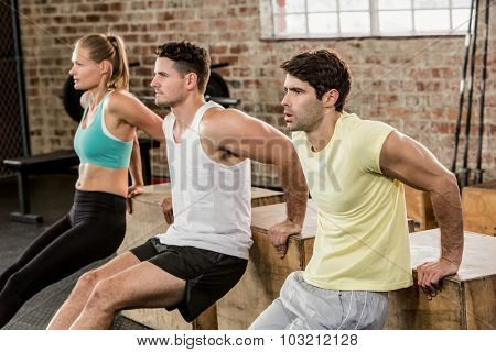 Cropped image of people holding plyo box and exercising at the gym
