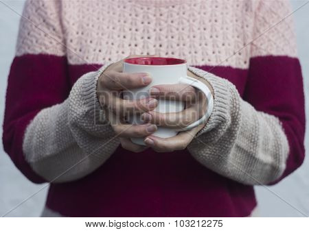 A woman holds a hot cup of tea and warms his hands