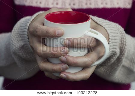 Soft and blur conception.A woman holds a hot cup of tea and warms his hands