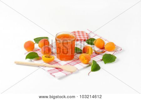 glass jar with homemade apricot marmalade, accompanied by wooden spoon and fresh apricots