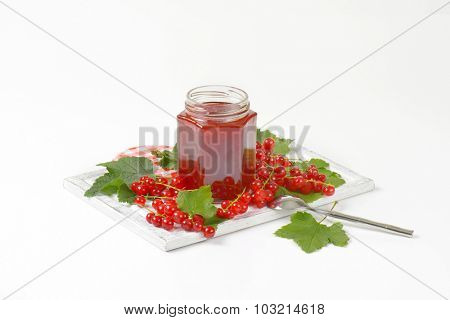 glass jar of red currant jam standing on the wooden cutting board with fresh red currant