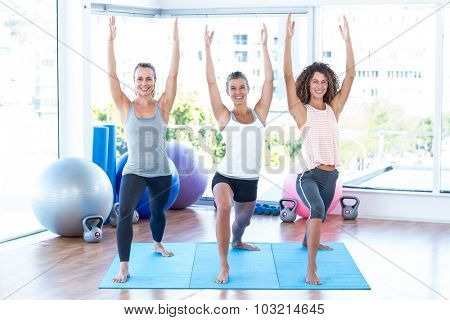 Smiling woman with arms raised in fitness studio