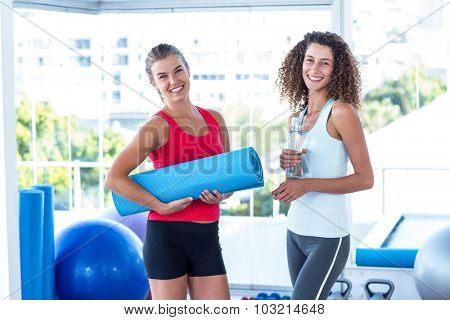 Portrait of fit women holding exercise mat and water bottle in fitness studio