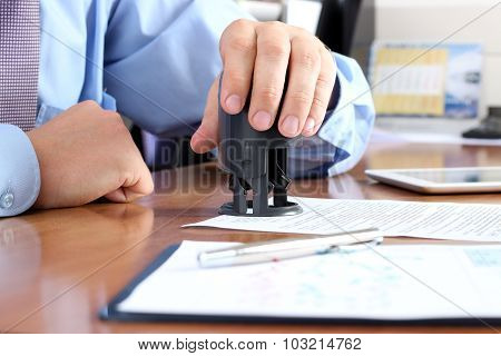 Close-up Of Businessman Hand Pressing A  Stamp On Document In The Office