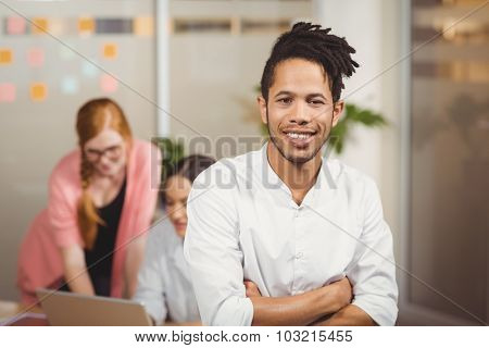 Portrait of smiling businessman with arms crossed in office with female colleagues working in background