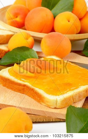 crunchy white toast bread with apricot jam, served on the wooden cutting board